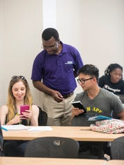Prof. Douglas Magomo helps Breahna Claytor and Tim Garcia with their graphing calculators during a statistics class at Florida Southwestern State College on Thursday, July 5, 2018, in Fort Myers.
