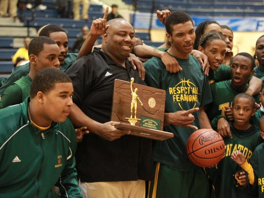 Taft coach Mark Mitchell and team hold their trophy as they celebrate on the court after beating Summit County Day in the 4th period. Summit County Day High School battles Taft High School in a division III regional final game at Fairmont Trent Arena Saturday March 19, 2011 in Kettering, Ohio. Taft won 49 to 45 over Summit County Day.