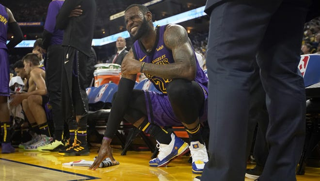 Los Angeles Lakers forward LeBron James grimaces after straining his left groin, during the second half of the team's game against the Golden State Warriors on Tuesday in Oakland, Calif.