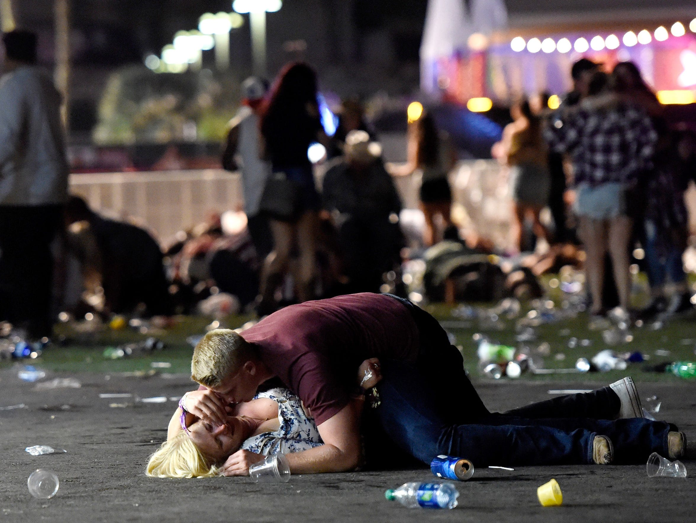 A man lays on top of a woman as others flee the Route 91 Harvest country-music festival after a shooter opened fire on the festivals grounds on Oct. 1, 2017.