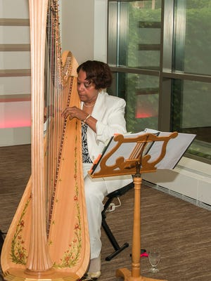Dorothea Fields plays her harp at the 2013 Rise and Shine breakfast.
