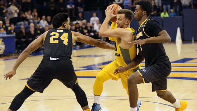 Marquette's Andrew Rowsey looks for a way to the basket between UWM's Bryce Nze and Carson Warren-Newsome during the teams' scrimmage Sunday at the Al McGuire Center.