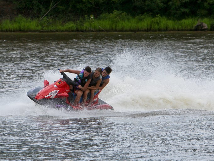 Penny and Makayla Johnson and Blaine Sadler zoom across the Ouachita River on a jet ski on Labor Day Monday.