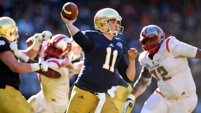 Dec 28, 2013; Bronx, NY, USA; Notre Dame Fighting Irish quarterback Tommy Rees (11) throws a pass against the Rutgers Scarlet Knights during the first half of the Pinstripe Bowl at Yankees Stadium. Mandatory Credit: Joe Camporeale-USA TODAY Sports