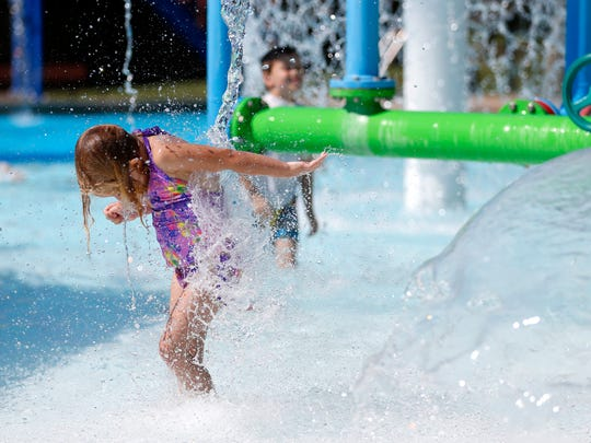 Elsie Bumgardner, 5, gets hit by water as she runs under a water feature at Silver Springs pool on Thursday, June 28, 2018. The Park Board is keeping pools open late as the National Weather Service issued Heat Advisories.