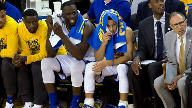 Golden State Warriors forward Draymond Green (23) and guard Stephen Curry (30) on the bench against the Oklahoma City Thunder during the fourth quarter in game one of the Western conference finals of the NBA Playoffs at Oracle Arena.
