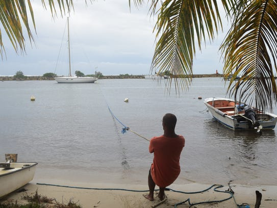 A man pulls in a boat ahead of Hurricane Maria in the