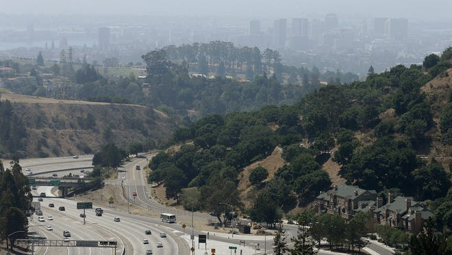 The city of Oakland, Calif., is seen through a haze that covers the skyline Monday, Aug. 17, 2015.
