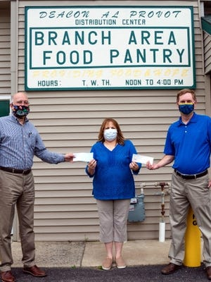 Brad Rockey, Sunrise Rotary Club member and C19 Relief Task Force Leader, along with Scott Ohm, Coldwater Noon Rotary Club present Patti Daoud, Branch Area Food Pantry manager, with checks from the clubs for the food pantry.