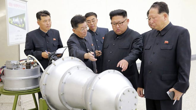 This undated picture released by North Korea's official Korean Central News Agency (KCNA) shows North Korean leader Kim Jong-Un (C) looking at a metal casing with two bulges at an undisclosed location.