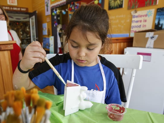 File - Alexia Cooley, 8, works on painting her Snoopy