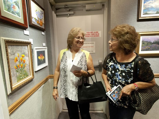Gloria Peterson, Orosi, left, Irene Rodriguez, Cutler, right, check out paintings done by artists from the Tulare Senior Center on Thursday. The Tulare Historical Museum is hosting a new exhibit featuring artists from art classes at the Tulare Senior Center. The museum hosted an artists' reception to kick off the exhibit.