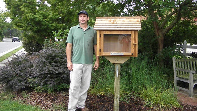 AndyNunnally stands with the Little Free Library he helped design and install at the corner of Ames and Market streets, in Onancock.