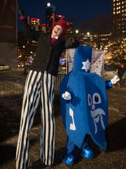 Stilt walker Eric Baker of Detroit Circus poses with a giant dreidel during the 7th annual Menorah in the D celebration.