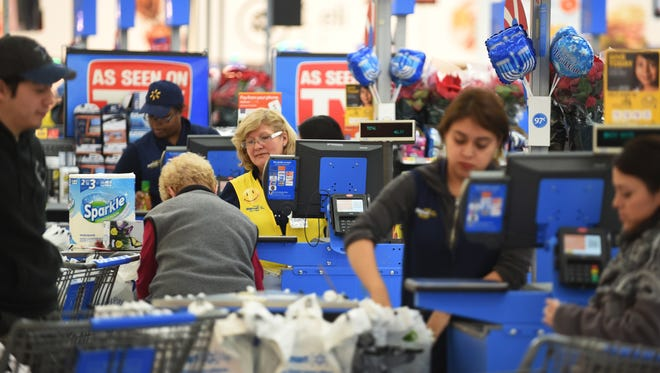 This is for Walmart's prep for the Thanksgiving Black Friday. Cashiers take care of customers at Walmart in Seacacus , November 21, 2017.