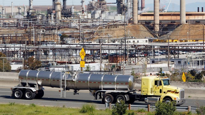 A tanker truck passes an oil refinery in Richmond, Calif.