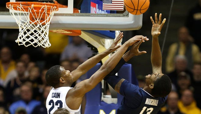Marquette freshman wing Jamal Cain and Xavier Musketeers forward Naji Marshall fight for a rebound on Wednesday.