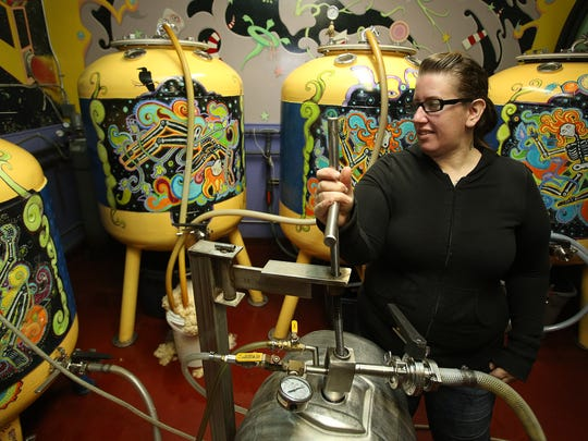 Jen Kent transfers Ruby beer from a fermentation tank into a keg at  McMenamins Tompson Brewery.