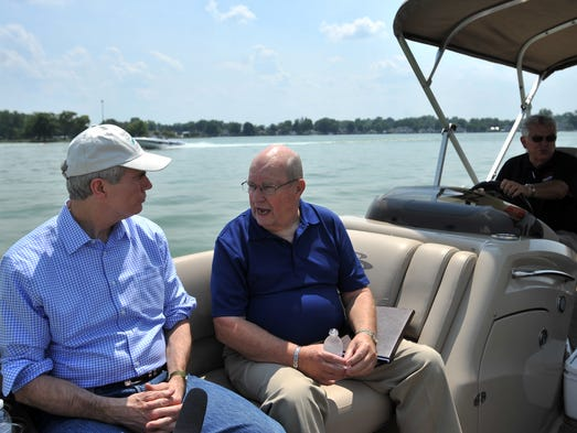 Merv Bartholow, center, director of Buckeye Lake for Tomorrow, talks to U.S. Senator Rob Portman, Friday afternoon, Aug. 1, 2014, as they are taken a tour of Buckeye Lake by Fairfield County Commissioner and Buckeye Lake Marina owner Dave Levacy. Portman and his wife Jane came to the lake for a meeting with Bartholow, Levacy and other local, state and national representatives about the water quality of Buckeye Lake.