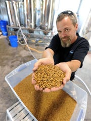 Mispillion River Brewing's Eric Williams shows off a handful of malt, which gives beer its color and flavor.