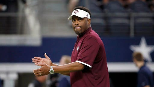In this Sept. 26, 2015 file photo, Texas A&M coach Kevin Sumlin applauds his team as players warm up for an NCAA college football game against Arkansas, in Arlington, Texas. The Aggies have lost some of the swag that came when Johnny Football took the Southeastern Conference by storm, Kevin Sumlin became a $5 million per year head coach and Texas A&M looked like it would be a perennial threat to Alabama.
