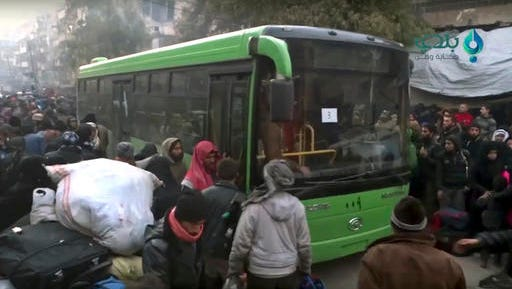 This frame grab from video provided by Baladi News Network, a Syrian opposition media outlet that is consistent with independent AP reporting, shows residents gather near a green government bus for evacuating from eastern Aleppo, Syria, Thursday, Dec. 15, 2016. The Russian military said over 1,000 people have been evacuated from Aleppo under a cease-fire deal reached with Syrian rebels. France's ambassador to the United Nations says international observers should monitor the safe evacuation of civilians and fighters from the war-torn Syrian city of Aleppo.