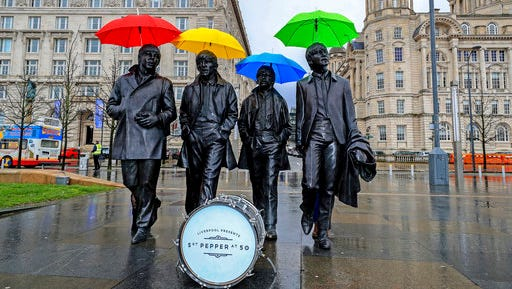 """Umbrellas are placed over the statute of the Beatles, during a photocall, on Liverpool's waterfront, in Liverpool, England, Wednesday, March 22, 2017. The city of Liverpool is getting set to celebrate the half-centenary of """"Sgt. Pepper's Lonely Hearts Club Band,"""" one of the most influential albums by local heroes The Beatles."""
