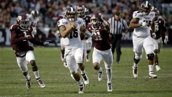 Mississippi State quarterback Dak Prescott (15) rushes for a first down as Texas A&M's De'Vante Harris (1) and Howard Matthews (31) pursue during the third quarter of an NCAA college football game Saturday, Nov. 9, 2013, in College Station, Texas. Texas A&M won 51-41. (AP Photo/David J. Phillip)