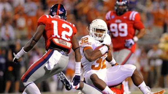 Texas running back Johnathan Gray (32) spins off a tackle while avoiding Mississippi defensive back Cliff Coleman (12) for a 19-yd gain during the fourth quarter in their NCAA college football game in Oxford, Miss., Saturday, Sept. 15, 2012. (AP Photo/Austin McAfee)