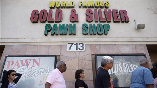 People wait in line to enter the Gold & Silver Pawn Shop in Las Vegas Monday, July 28, 2014, in Las Vegas.