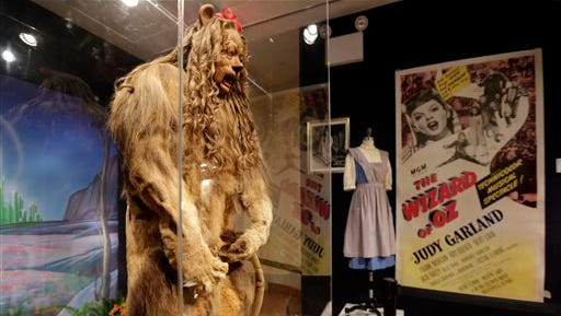 """This Nov. 21, 2014 photo shows Bert Lahr's Cowardly Lion costume and a three-sheet poster from """"The Wizard of Oz,""""  part of the """"There's No Place Like Hollywood"""" movie memorabilia auction at Bonhams auction house in New York. Lahr's costume will be auctioned with other Hollywood items Monday, Nov. 24, 2014, in New York. (AP Photo/Richard Drew)"""