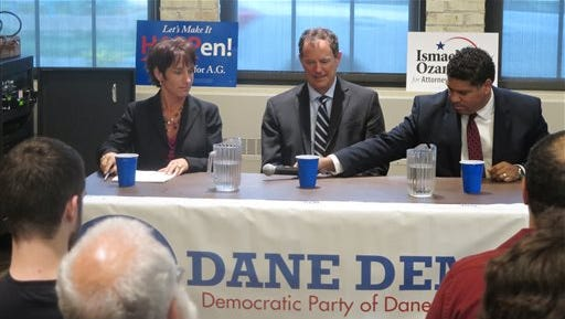 Dane County District Attorney Ismael Ozanne, right, passes a microphone to Jefferson County District Attorney Susan Happ, left, on Tuesday, July 22, 2014, at a forum in Madison, Wis., for all three Democratic candidates for Wisconsin attorney general, as state Rep. Jon Richards, center, watches. The candidates will square off in a primary Aug. 12.