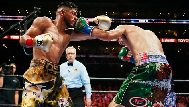 Abner Mares, left, battles Leo Santa Cruz during the 12th round of their championship bout in August of 2015. Mares, who is trained by Oxnard's Robert Garcia, will face Jesus Cuellar on Saturday night at USC. Cuellar's WBA World featherweight title will be on the line.