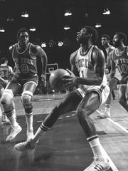Oscar Robertson looks toward the basket as Willis Reed of the New York Knicks comes over to defend on Nov. 22, 1973, in Milwaukee.