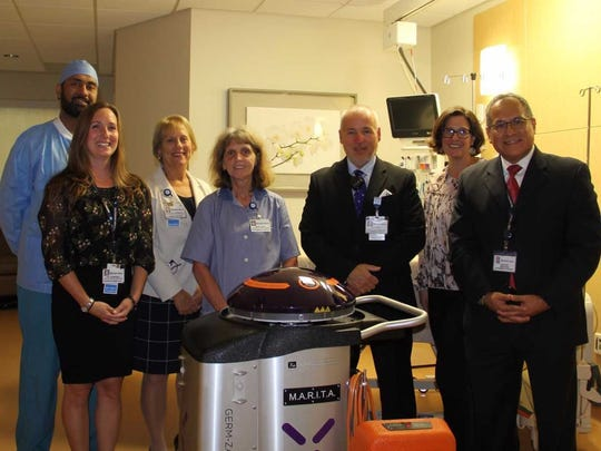 Posing with MARITA, Hunterdon Medical Center's new disinfecting robot, are Lisa Rasimowiz,  director of Infection prevention; Harkanwal Sandhu, lead operating room, environmental service worker; Patricia Steingall,  vice president of patient care service and chief nursing officer; Marie Davis, lead environmental service worker; Bill Farrell, assistant director, environmental services, Elizabeth Arnold, infection preventionist and Jose Diaz, director, environmental services.