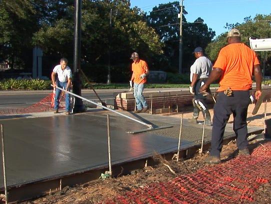 Crews work on the sidewalks outside of Doak Campbell