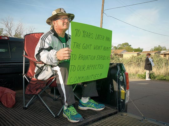 In this 2015 file photo Patrick Garcia holds a sign in front of a caravan at the Tularosa High School parking lot about to leave for the Trinity Site. Garcia wanted to raise awareness of the negative health impacts stemming from the atomic bomb test which took place at the Trinity Site in 1945.