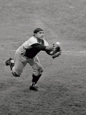 Catcher Yogi Berra of the New York Yankees grabs for a foul pop bunted by pitcher Tony Pena of the Kansas City Athletics in the eighth inning of the game at New York's Yankee Stadium, September 2, 1962. Yankees won 2-1.(AP Photo)