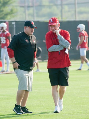 Nick Petrino, left, chats with his father,  University of Louisville Cardinals' football head coach Bobby Petrino, during the team's first practice of the season. Nick is an assistant coach on his father's team.