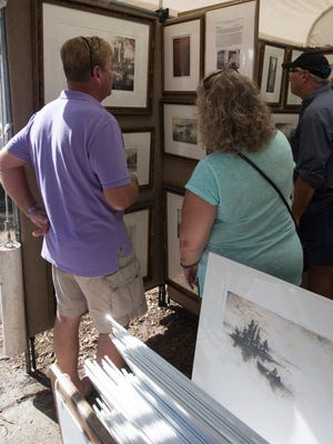 Ken Browning and his wife, Carol, check out the art on display at the Great Gulfcoast Arts Festival in Seville Square Friday, Nov. 3, 2017.