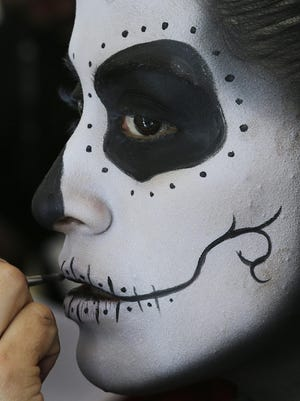 A woman gets her face painted in preparation for a Day of the Dead parade to begin along Mexico City's main Reforma Avenue, Saturday, Oct. 29, 2016. Mexico's Day of the Dead celebrations, which traditionally consisted of quiet family gatherings at the graves of their departed loved ones are fast changing under the influence of Hollywood movies, zombie shows, Halloween and even politics.