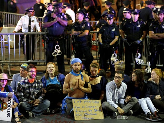 Protesters sit at the intersection of Wall Street and Broad Street in New York. The protesters, many who were affiliated with Occupy Wall Street, were trying to draw attention to the connection between capitalism and environmental destruction.  Eventually more than 50 protesters who would not move from the intersection were taken into custody.