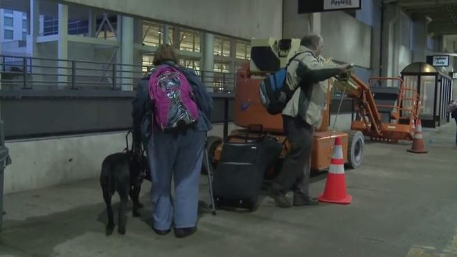 A still shot taken from the video shows Fred Wurtzel stopped by heavy equipment on the sidewalk. Mary Wurtzel and her dog Felix are coming up to the machine.