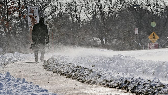 Snow blew across the sidewalk as a man walked along S. Lake Drive in St. Francis near Sheridan Park. Low wind chills are forecast for Wednesday, Wednesday night and Thursday will give way on Friday to another snow storm.