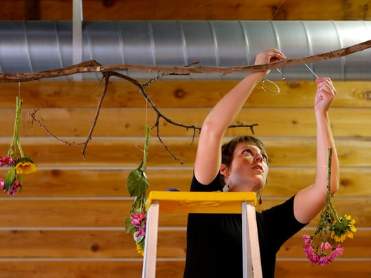 September 18, 2016 - Rev. Lucy Waechter Webb, pastor of Evergreen Presbyterian Church hangs fresh cut flowers inside the church before that start of Sunday service. Evergreen sold their former home, along with the 9.7 acres of land under it to Rhodes College and has settled into a humble 6,500 square foot building on Overton Park. (Mike Brown/The Commercial Appeal)
