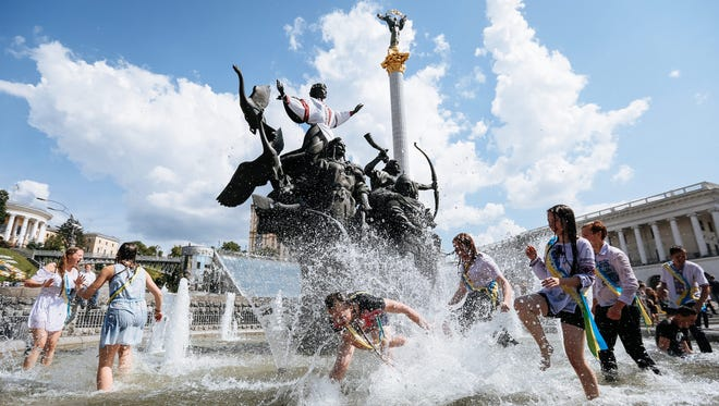 Ukrainian students play in a fountain as they celebrate the end of their school term on Independence Square in downtown Kiev, Ukraine, May 27, 2016. The square was the scene of battles with security forces in 2014.