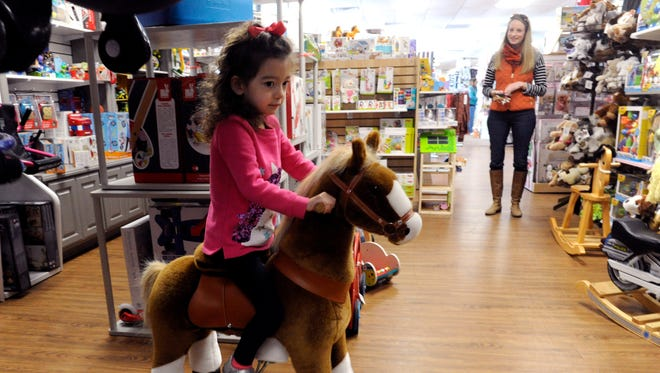 Catherine Collins watches her 4-year-old daughter Gabriella Vecino try out a riding toy Wednesday at Little Giant Kidz. Saturday is Small Business Saturday, where shoppers are encouraged to patronize local stores.
