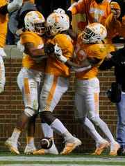 Tennessee defensive lineman Jonathan Kongbo, center, celebrates with teammates after returning an interception for a touchdown during the second half Saturday at Neyland Stadium.