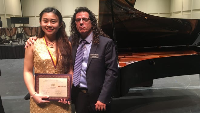 Xuesha Hu, winner of the eight Bösendorfer USASU International Piano Competition, poses with contest president Baruch Meir after her winning performance Jan. 8, 2017, at Symphony Hall in Phoenix.