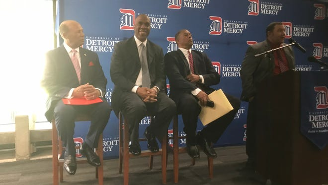 Mike Davis, flanked by Detroit Mercy President Antoine M. Garibaldi, is all smiles as he is introduced as the school's 22nd head basketball coach.